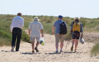 Group of people walking in sand dunes