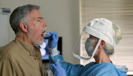 Man being tested for Covid-19 by healthcare worker in PPE