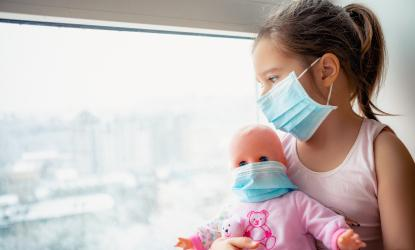 Little girl and doll wearing face masks sitting in window