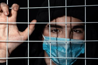 Person wearing facemask behind bars