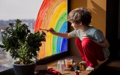 Young boy drawing rainbow on a window