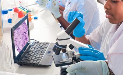Scientist examning human tissue under a microscope
