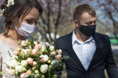Bride and groom wearing protective masks