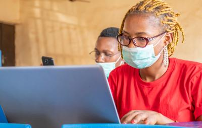 African students wearing facemasks and using a laptop
