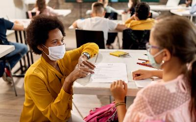 Teacher and young girl in a classroom wearing facemasks