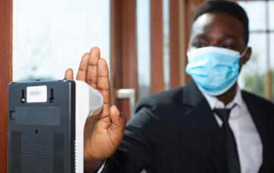 A black man wearing a suit and an anti-virus mask is using his hand to scan his body temperature