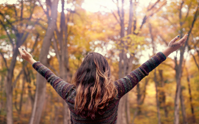 Woman with arms outstretched standing amongst trees