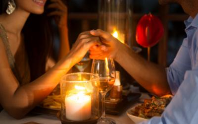 Romantic couple holding hands over a candlelit dinner