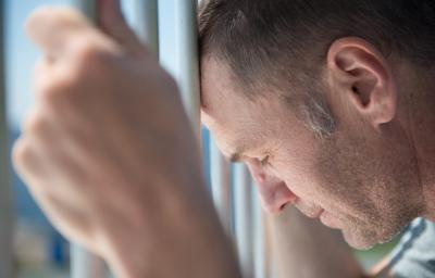 Male inmate holding prison bars