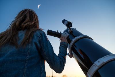Girl looking at moon through telescope