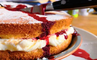 Victoria Sponge cake with a knife curring through it