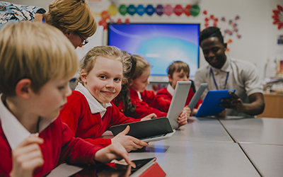 Pupils seated in a classroom, looking at iPads