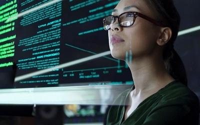 Photo of a woman looking at a computer screen, with computer screen text behind her too.