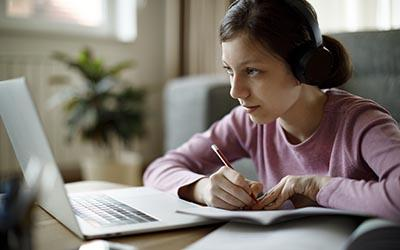 Teenage girl using laptop for studying at home