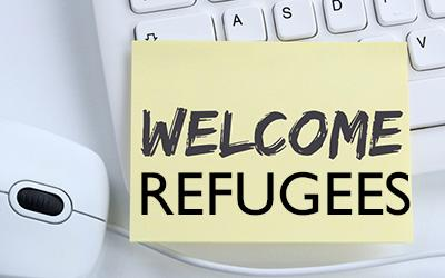 A 'Welcome Refugees' note on a computer keyboard, next to a mouse