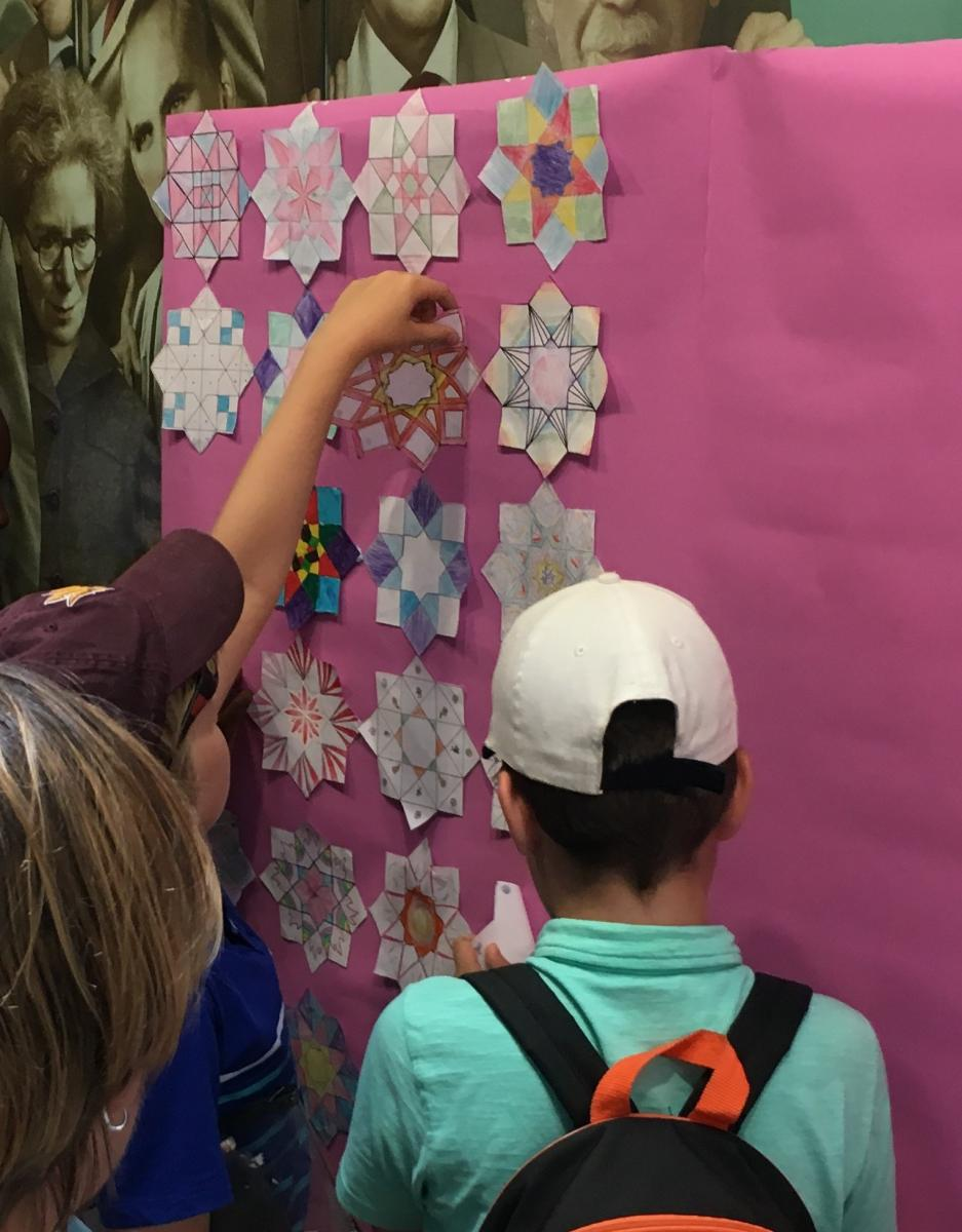 Children posting mathematical designs to a poster board