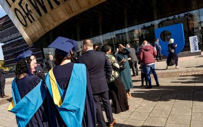 Graduates standing in front of Wales Millenium Centre